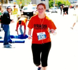 Woman smiles during a run race.