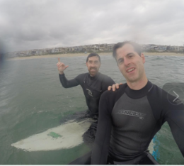 Two men in wetsuits paddling on boards in the ocean