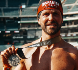 Henry poses with his Spartan race finisher medal.