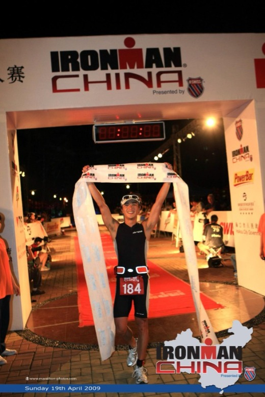 Male athlete holds up finishing banner at Ironman China