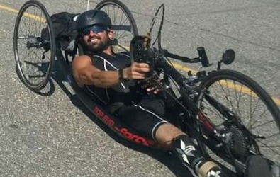 Athlete smiles and races in a handcycle in a triathlon.