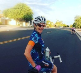 Women smiles while holding water bottle sitting on her bike.