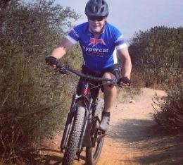 John rides his mountain bike down a dirt trail