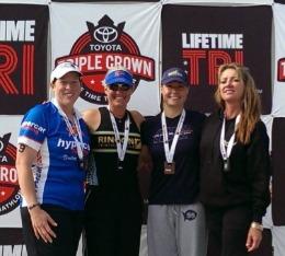 4 Female athletes pose on stage after Lifetime Triathlon