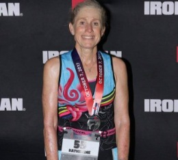 Katie poses for picture with her medal after Ironman triathlon