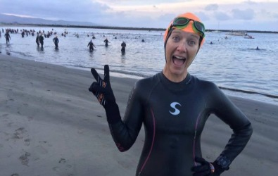 Sarah gives the peace sign while waiting for the start of her triathlon swim.