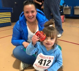 Mom and daughter pose with finisher medal.
