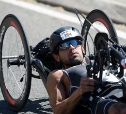 Man racing in a handcycle in a half-ironman triathlon.