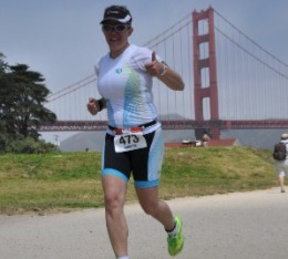 Female athletes gives thumbs up during run in triathlon