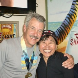 John with his wife and a finisher medal around his neck.